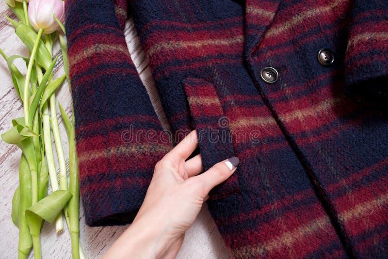 一件方格的外套,一只女性手,郁金香的口袋 时兴的概念,细节 免版税库存图片