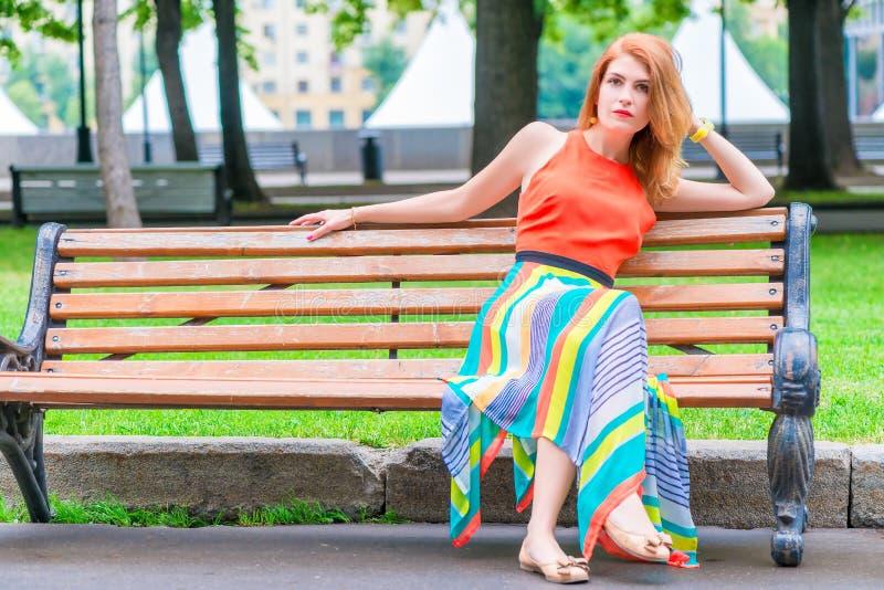 一件明亮的橙色礼服的女孩在长凳 免版税库存图片