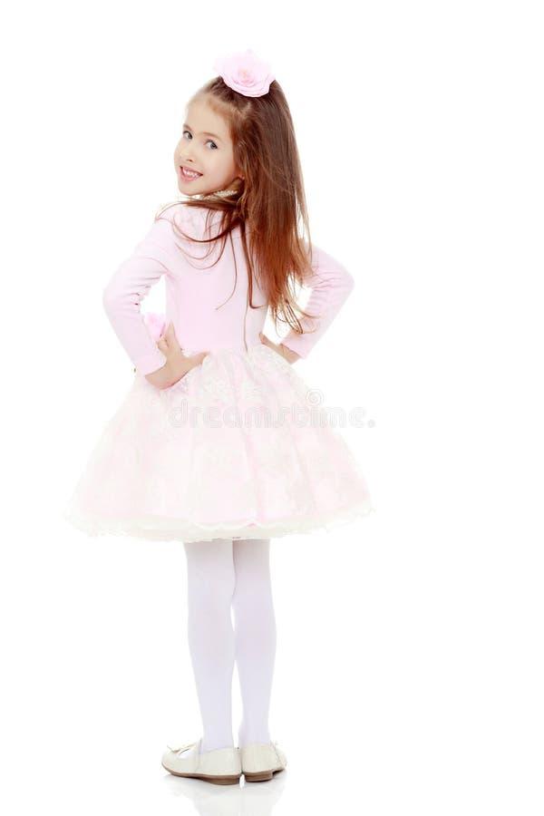 一件桃红色礼服的典雅的小女孩 免版税库存照片