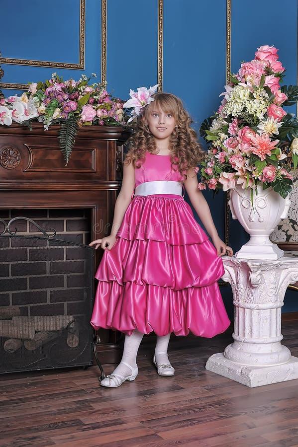 一件桃红色礼服的女孩在花中 库存照片