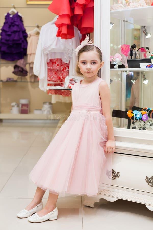 一件桃红色礼服的美丽的女孩在商店 图库摄影