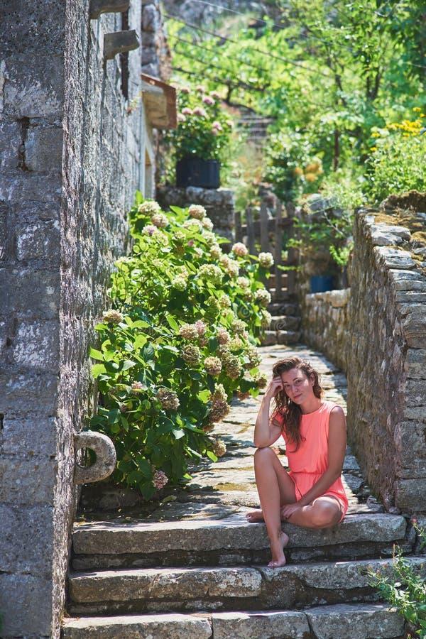 一件桃红色礼服的美丽的被晒黑的女孩摆在对一个古老中世纪石房子的墙壁 免版税图库摄影