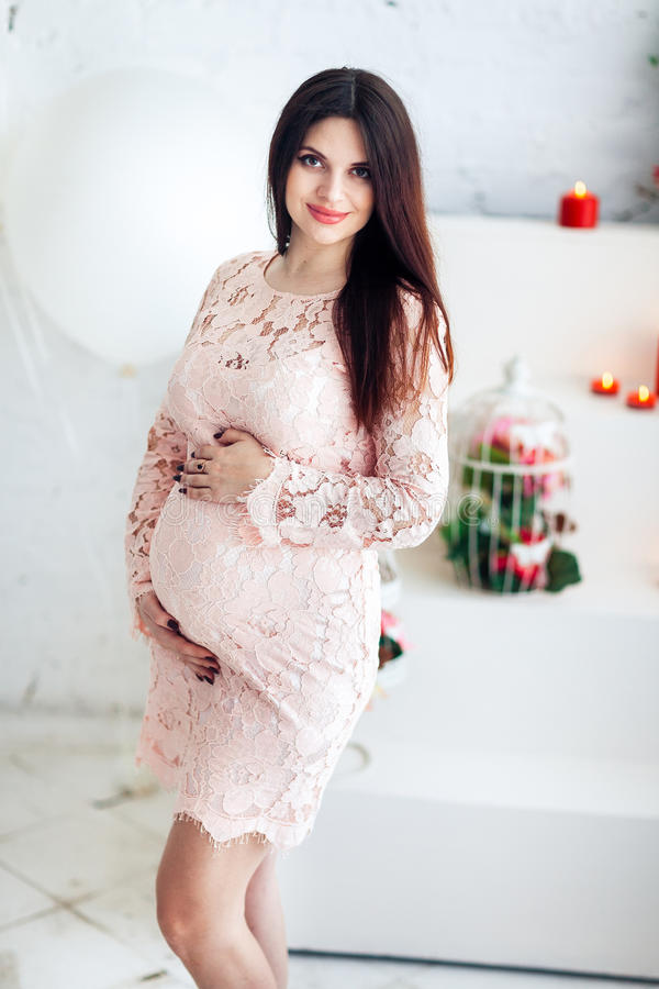 一件桃红色礼服的年轻人孕妇对看照相机的白色墙壁 免版税库存图片