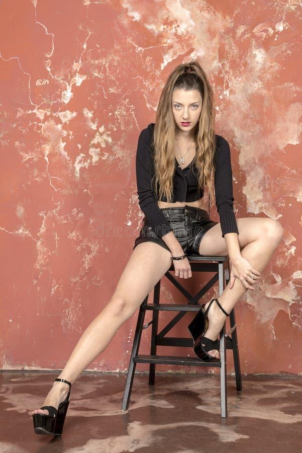 一件黑毛线衣和皮革短裤和平台凉鞋的年轻长发长腿的皮包骨头的女孩 免版税库存图片