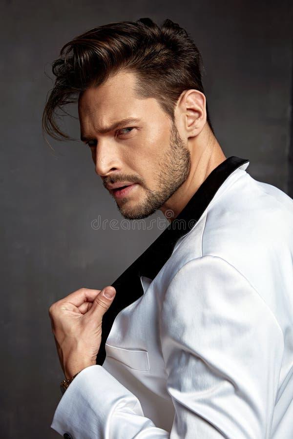 一件深色头发的年轻模型佩带的白色夹克的画象 免版税库存图片