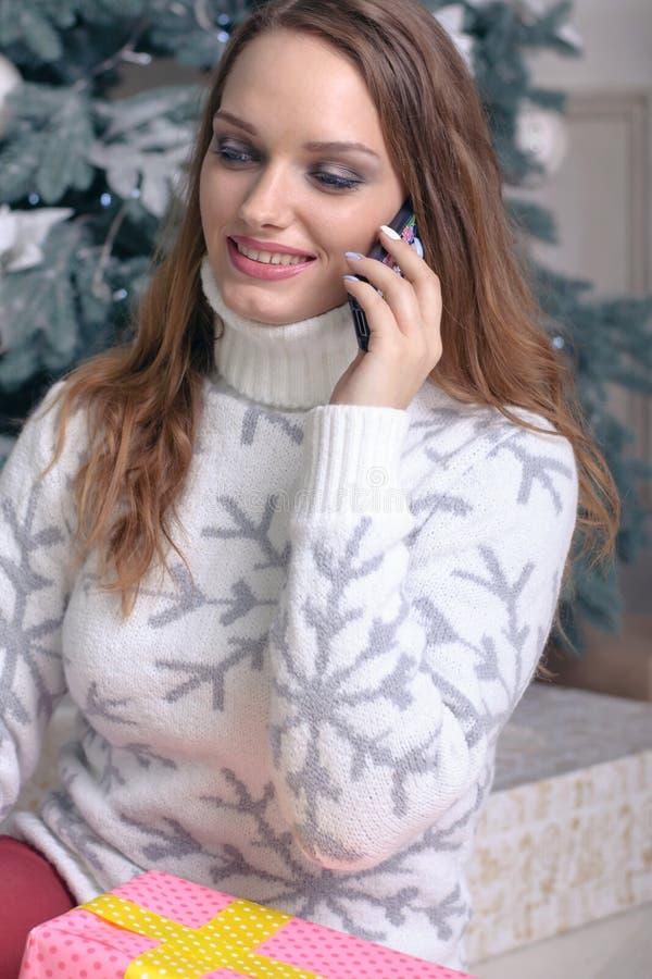 一件温暖的毛线衣的女孩在电话里说 免版税图库摄影