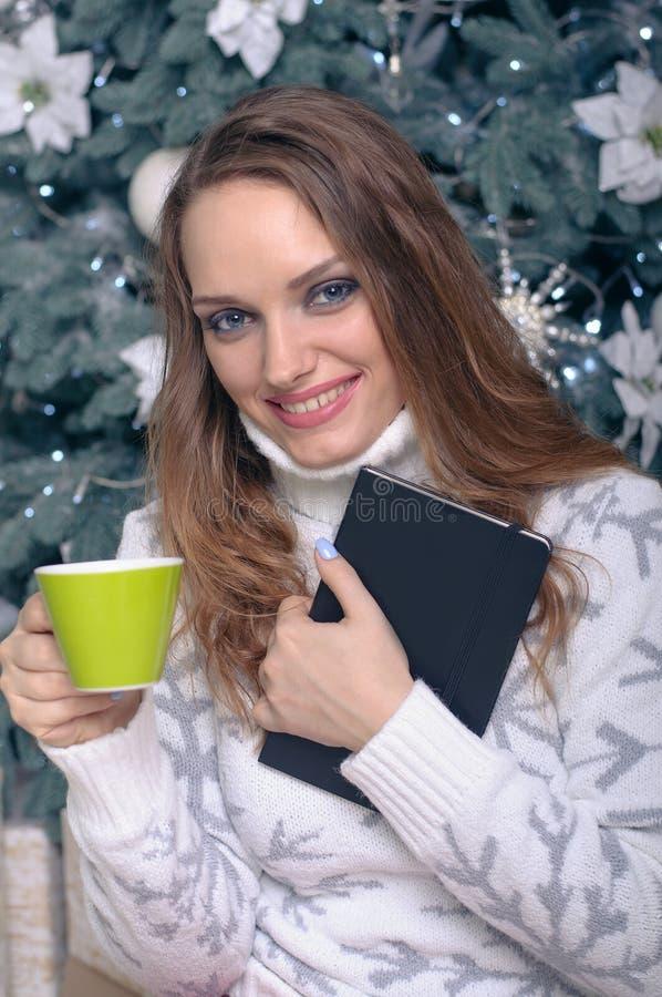 一件温暖的毛线衣的妇女有一杯茶的 免版税库存图片
