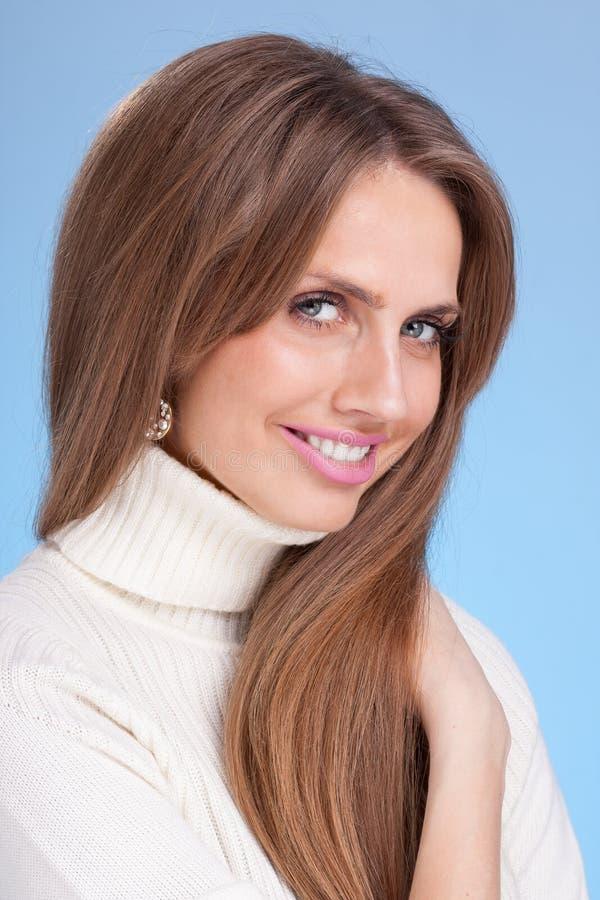 一件温暖的毛线衣的年轻可爱的妇女在蓝色背景 免版税库存图片