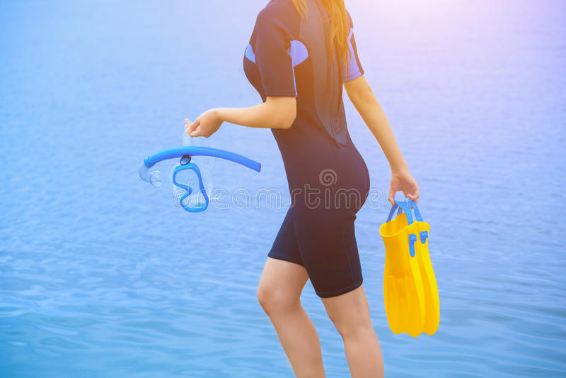 一件潜水衣的女孩潜水者拿着与一支蓝色管在她的手上和黄色飞翅的一个面具在另一只手上 免版税库存照片