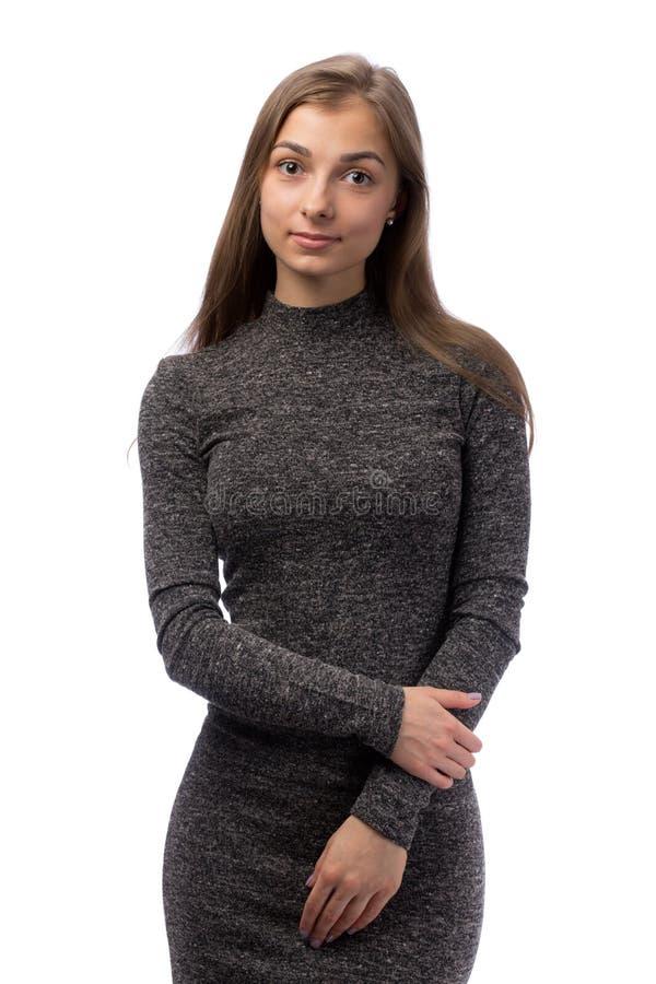 一件灰色礼服的亭亭玉立的迷人的女孩在演播室 免版税库存照片