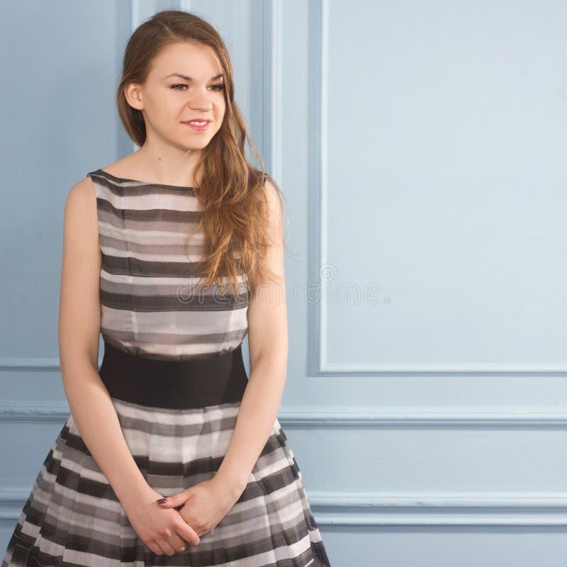 一件灰色礼服的美丽的女孩在蓝色墙壁附近 免版税图库摄影