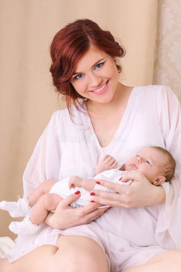 一件白色丝绸礼服的愉快的年轻母亲,抱着她的婴孩 库存图片
