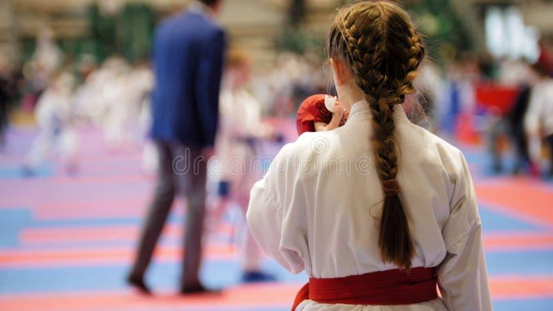 一件白色和服的空手道女孩有准备好红色的传送带的战斗 免版税库存图片