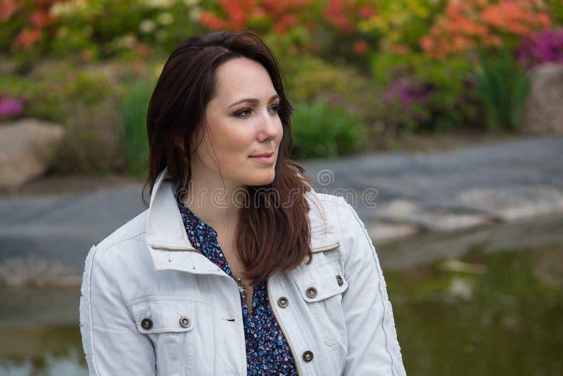 一件白色夹克的美丽的妇女在庭院里 库存图片
