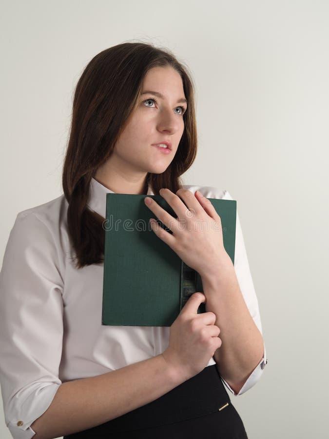 一件白色女衬衫的女孩有一本旧书的教诗歌 免版税库存照片