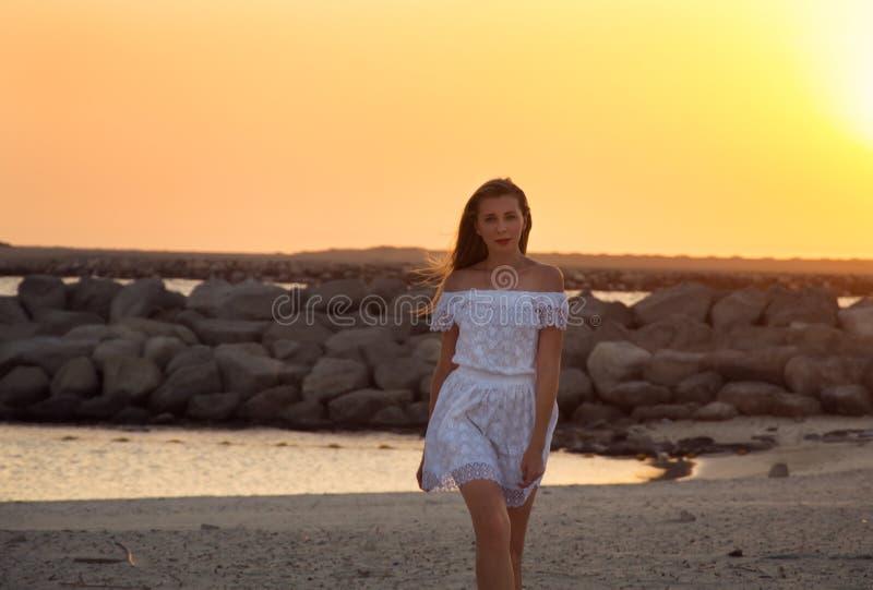 一件白色礼服的女孩在日落 库存照片