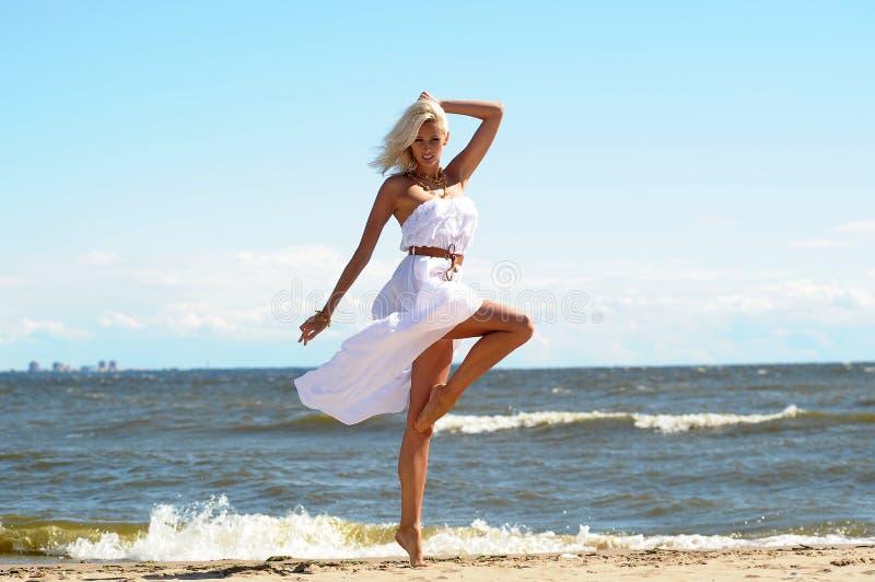 一件白色礼服的女孩在海滩 库存图片
