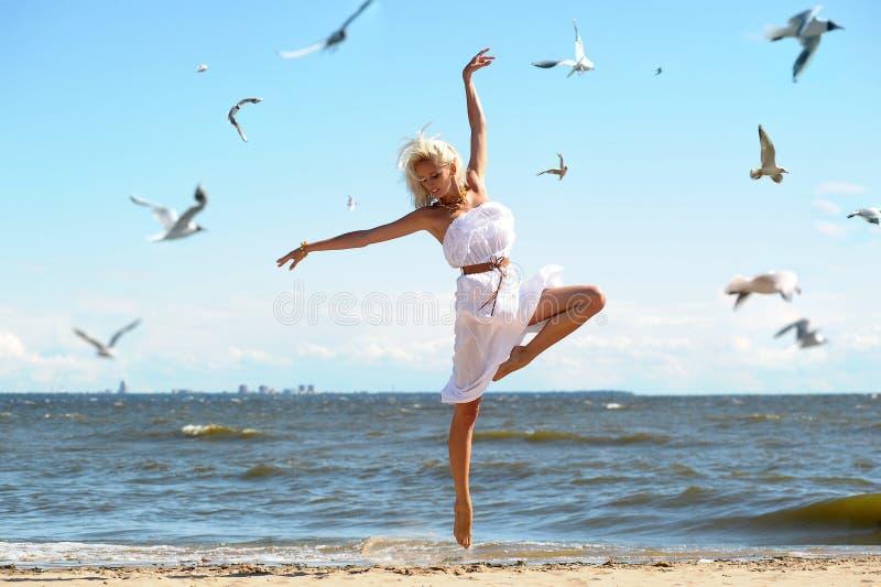 一件白色礼服的女孩在海滩 图库摄影