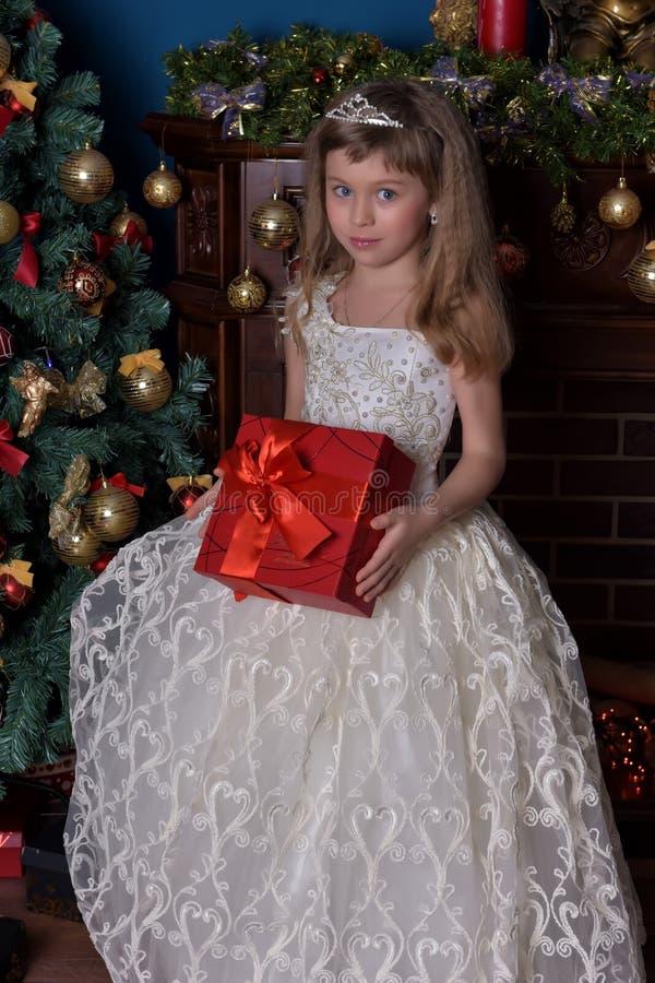 一件白色礼服的女孩有一个红色箱子的 免版税库存照片