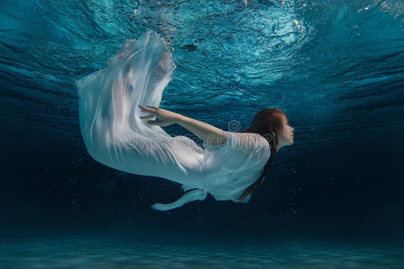 一件白色礼服的妇女在水下 免版税库存照片