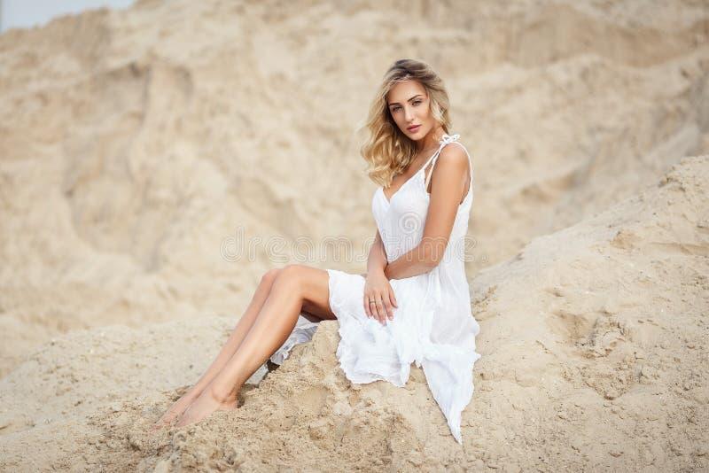 一件白色礼服的美丽的妇女在沙漠 免版税库存照片