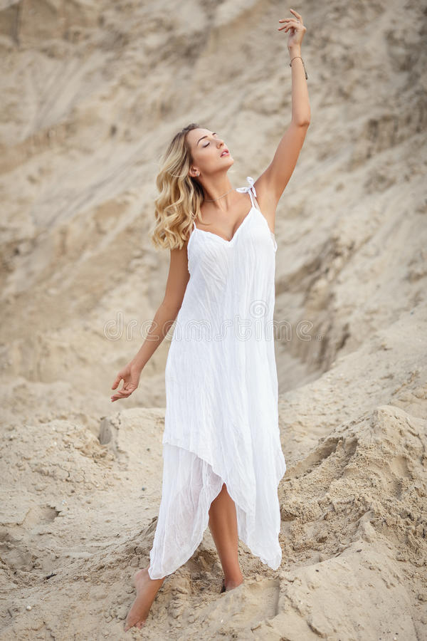 一件白色礼服的美丽的妇女在沙漠 图库摄影