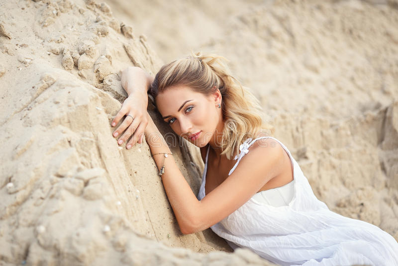一件白色礼服的美丽的妇女在沙漠 免版税库存图片
