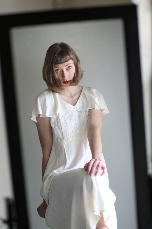 一件白色礼服的美丽的妇女在镜子反射了 图库摄影