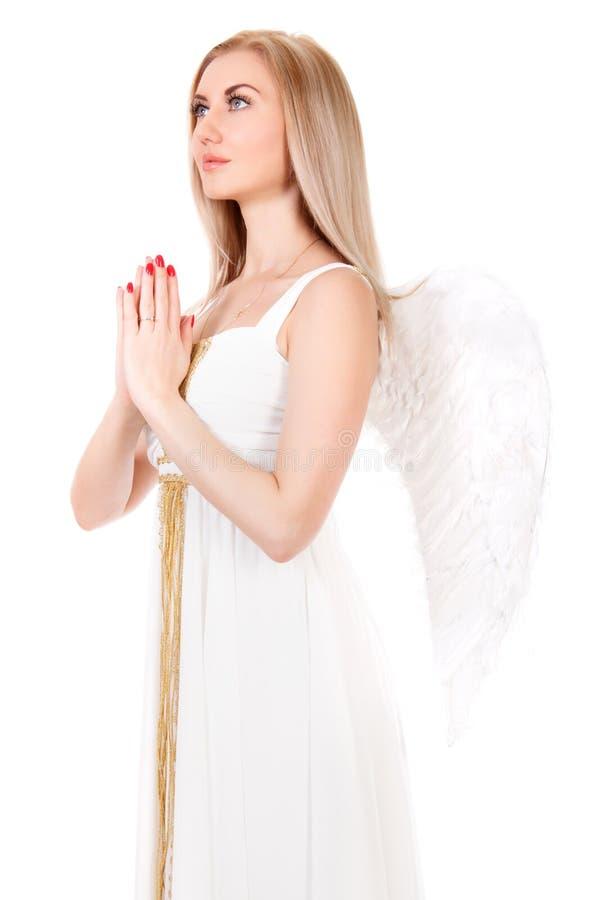 一件白色礼服的美丽的祈祷的少妇有天使的飞过 图库摄影