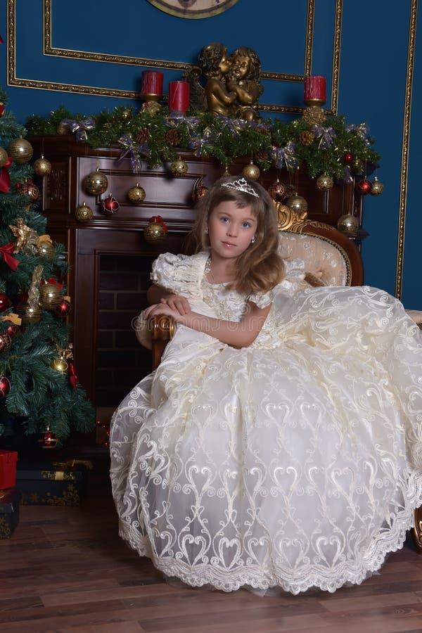 一件白色礼服的年轻公主有在她的头的一个冠状头饰的在圣诞树 库存图片
