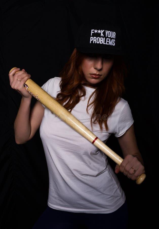 一件白色衬衣的年轻少年女孩,黑盖帽,摆在与棒球棒 光和影子作用 图库摄影