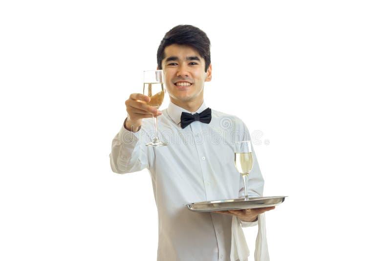 一件白色衬衣的年轻英俊的侍者舒展向前玻璃酒和微笑 库存图片