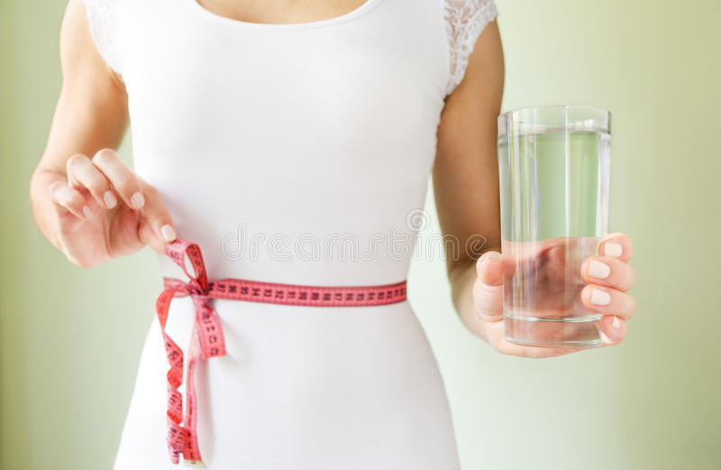 一件白色紧的礼服的苗条运动妇女有在她的腰部附近的一卷测量的磁带的在她的手上拿着杯水 库存图片