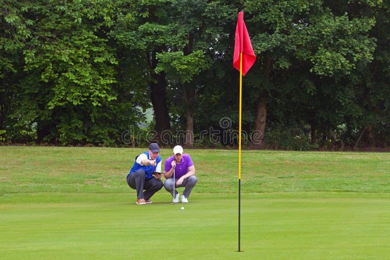 读轻轻一击的线高尔夫球运动员和小型运车 库存图片
