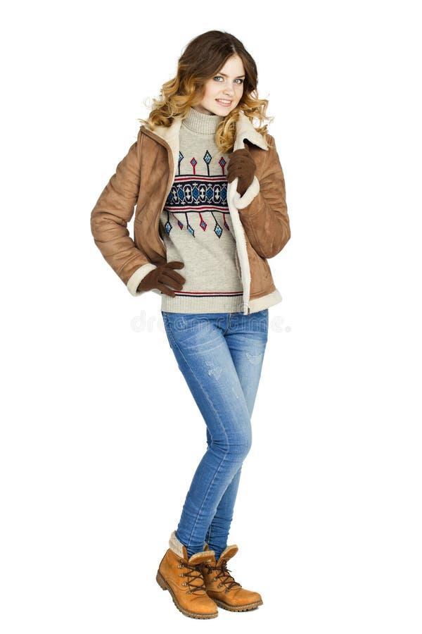 一件皮革紧身连衫外套和蓝色牛仔裤的年轻美丽的女孩 库存照片