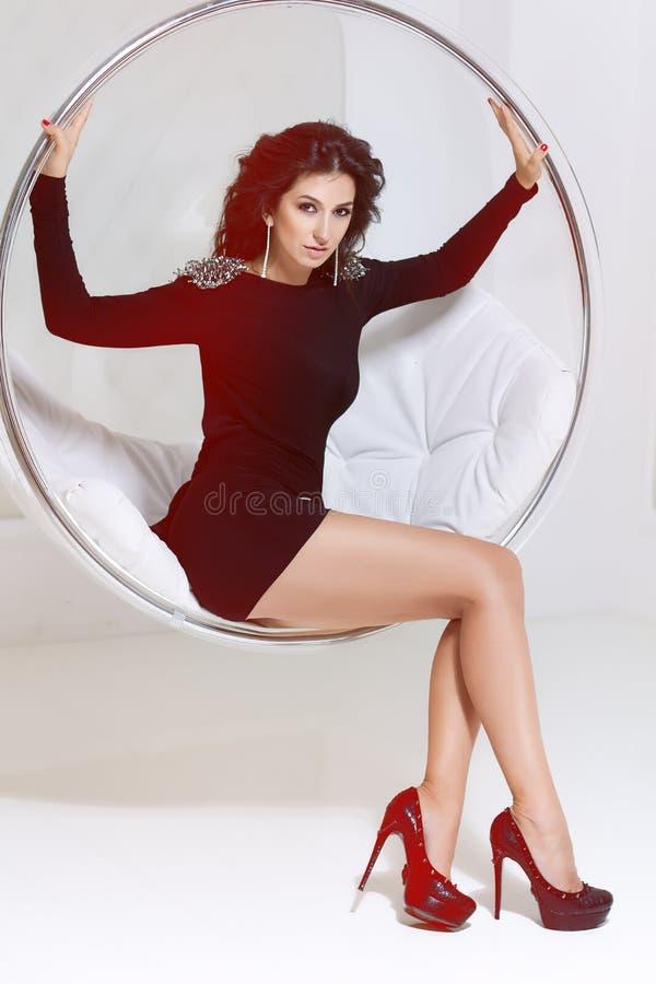 一件黑短的苗条的礼服的美丽的性感的豪华穿着考究的少妇在坐在ch的金刚石耳环长的黑发 免版税库存图片