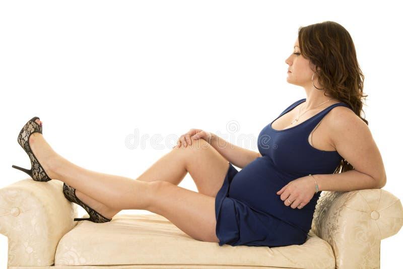 一件短的蓝色礼服坐的腿的孕妇在长沙发 免版税图库摄影