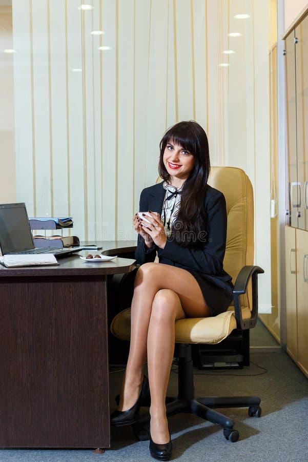 一份短裙饮用的咖啡的俏丽的妇女在办公室 免版税库存图片