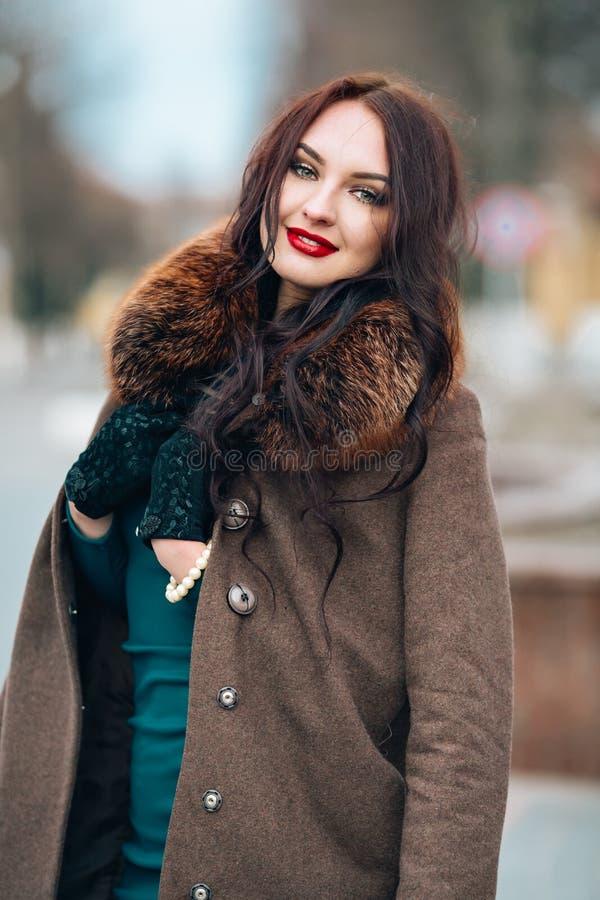 一件礼服和外套的美丽的女孩有毛皮衣领的 典雅的明亮的构成,红色嘴唇,看照相机 图库摄影