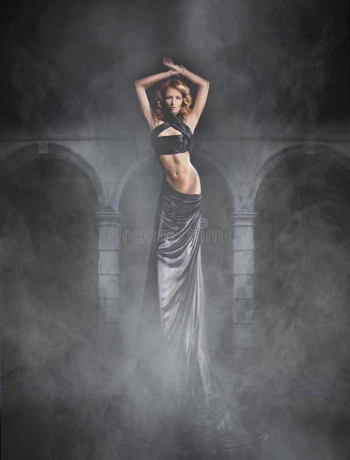 一件黑礼服的一个少妇在鬼的背景 图库摄影