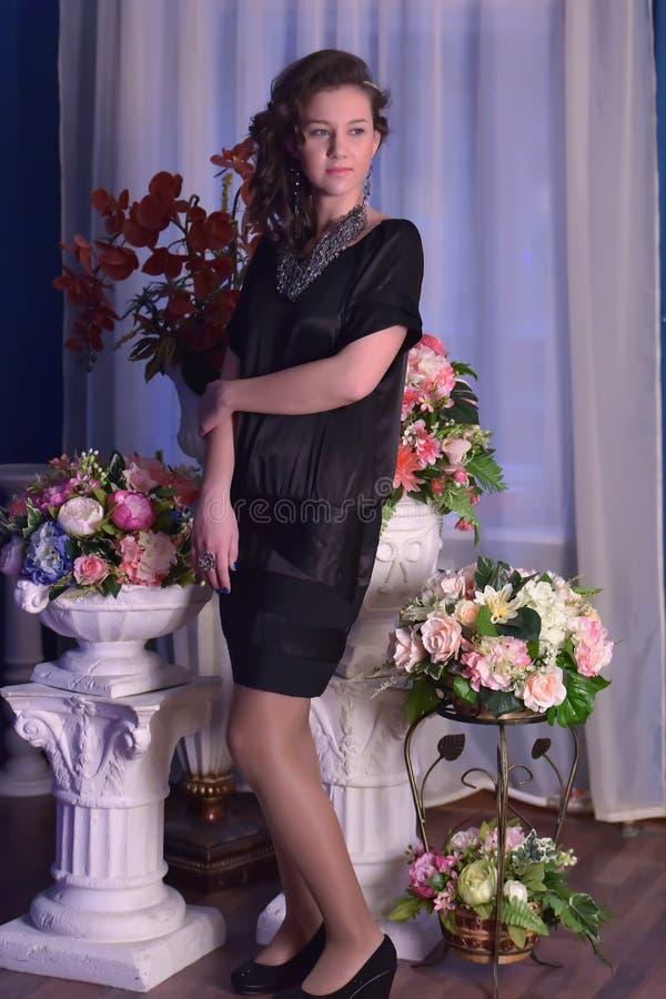 一件黑礼服的女孩在有花的一个花瓶旁边 免版税图库摄影