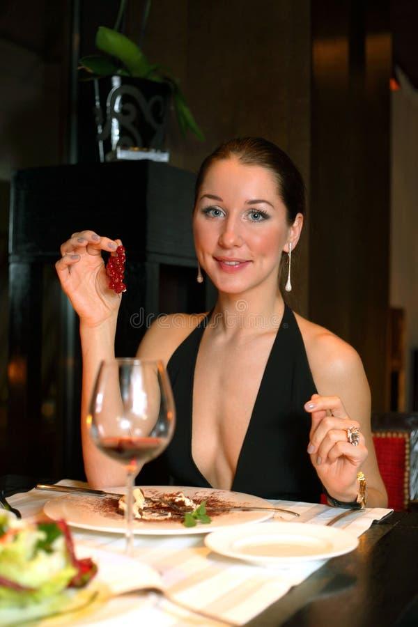 一件黑礼服的妇女用红色莓果 图库摄影