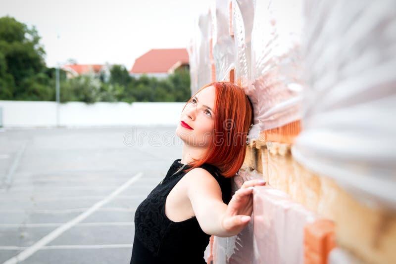 一件黑礼服的美丽的红发女孩站立在砖 库存照片