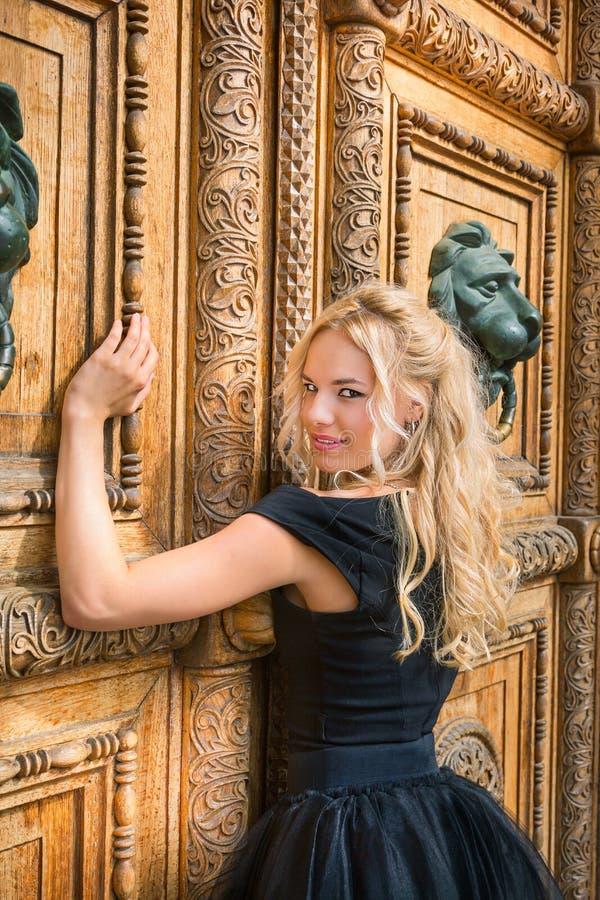一件黑礼服的金发碧眼的女人有大门的 概念的smal 库存图片