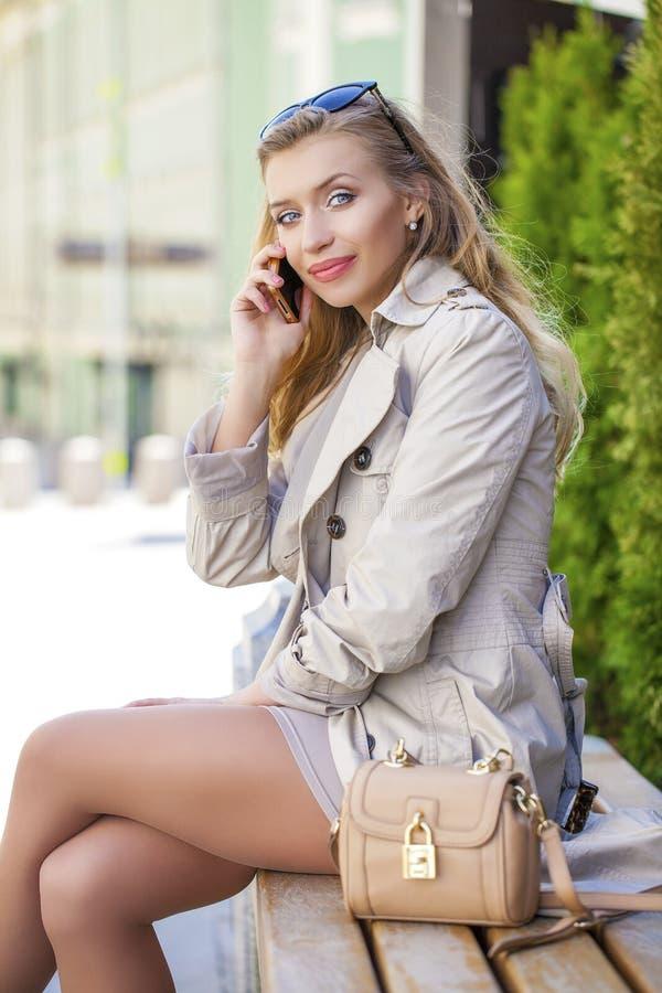 Download 一件米黄外套的年轻美丽的女孩,叫由电话,坐 库存图片. 图片 包括有 外套, 城市, 迷人, 特写镜头, 别致 - 62538621