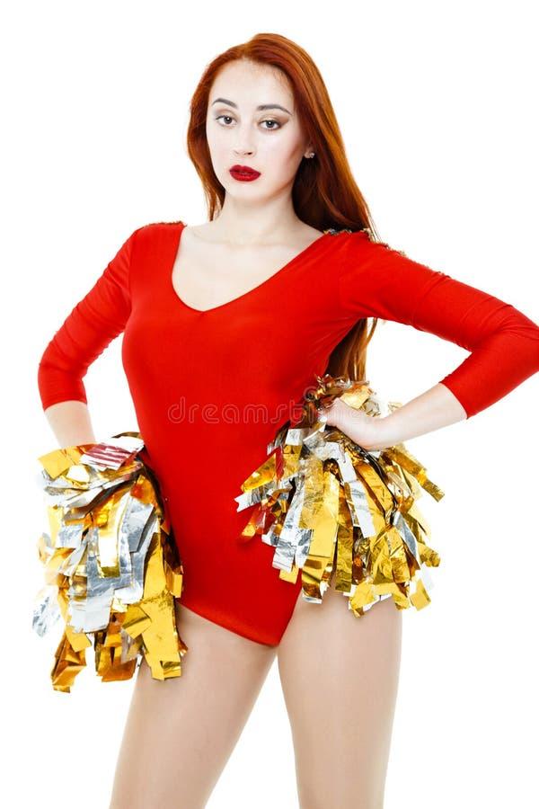 一件红色制服的美丽的年轻红发啦啦队员 免版税库存照片