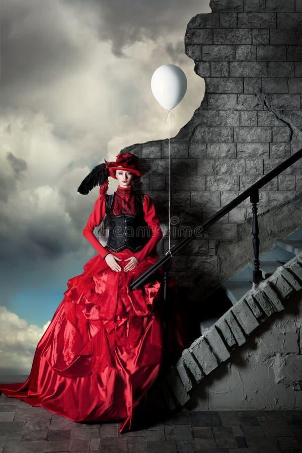 一件红色历史的礼服的妇女在风雨如磐的天空的背景站立 免版税库存图片