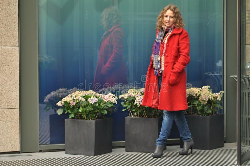 一件红色外套的美丽的女孩 免版税库存照片