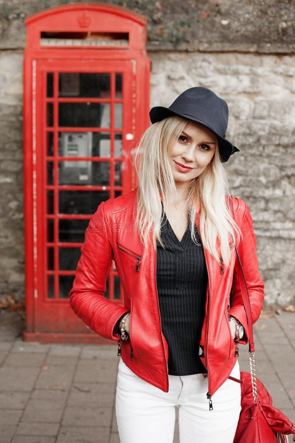 一件红色夹克的可爱的时髦少妇 库存图片