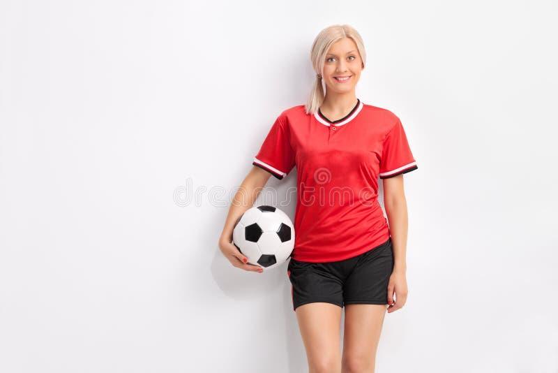 一件红色球衣的年轻女性足球运动员 免版税库存照片